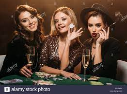 smiling attractive girls sitting at table in casino and looking at camera  Stock Photo - Alamy